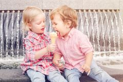 Two white Caucasian cute adorable funny children toddlers sitting together sharing ice-cream food. royalty free stock photo