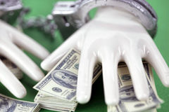 Two white ceramic  hands with handcuffs on pile of 100 dollar notes Royalty Free Stock Photos