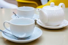 Two white ceramic tea mugs with shiny spoons and saucers. And a teapot stand on the table in a cafe Stock Photo