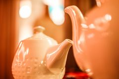 Two white ceramic teapots close up with blurred background royalty free stock photos