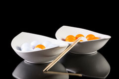 Two white ceramics bowls with golf balls Royalty Free Stock Photo