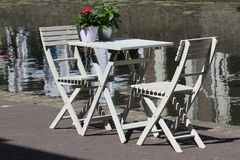 Two white chairs in from a delft canal. Relaxing place for a coffee in from water canal Royalty Free Stock Photography
