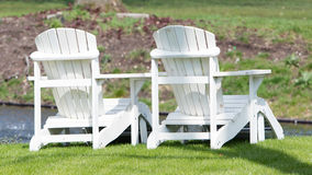 Two white chairs at the waterfront Royalty Free Stock Photos
