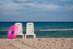 Two white chaise lounges and pink inflatable circle on the beach sand sea shore blue sky wave summer. Two white chaise longue and pink inflatable circle on the Royalty Free Stock Photography
