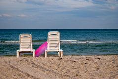 Two white chaise lounges and pink inflatable circle on the beach sand sea shore blue sky wave summer. Two white chaise longue and pink inflatable circle on the Stock Photos