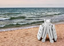 Two white chaise longue on sand on seashore. Beach. Two empty chaise lounges on a sandy beach against a blue sea background stock photos