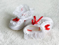 Two White children's bootees, shoes with red ribbons. Two White children's bootees, shoes with red bows and ribbons on a black background. Textile footwear for Royalty Free Stock Image