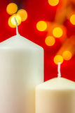 Two white christmas wax candles on red background Royalty Free Stock Photos