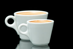 Two white coffe cups on the black background Stock Image