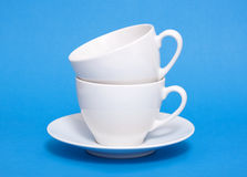 Two white coffee cup piled. On blue background Royalty Free Stock Photo