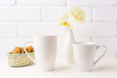 Two white coffee latte and cappuccino mug mockup with soft yello Royalty Free Stock Photo