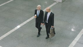 Two corporate executives arriving at modern office building. Two white collar corporate executives with coffee or bag in hand talking chatting while walking in stock video