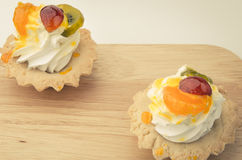 Two white cream cakes and pieces of fruit. Two white cream cupcakes and pieces of fruit on a wooden surface Stock Photos