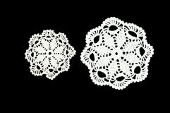 Two white crocheted coasters on the black background. Not isolated. Lace doily. Stock Image