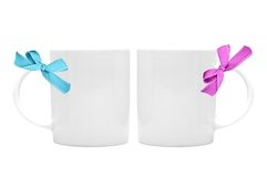 Two white cup with ribbon bow on white Stock Photo