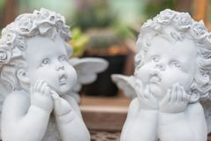 Two white cupid boys sculpture made of cement are in thinking action and looking to the sky stock images