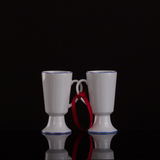 Two white cups on the associated with a red ribbon. Stock Photo