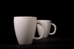 Two White Cups on Black Royalty Free Stock Image