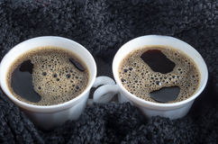 Two white cups with black coffee and foam are close Stock Image