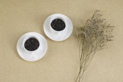 Two White cups with coffee beans on brown paper. Top view Royalty Free Stock Photos