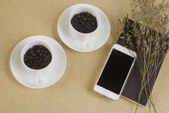 Two white cups with coffee beans and mobile phone. And notebook on brown paper. Top view Royalty Free Stock Photography