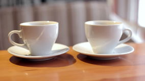 Two white cups of coffee a close-up. Hot drinks stock footage
