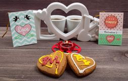 Two white cups of coffee, cookies in the shape of a heart, red candle and a Valentine card on a wooden table. On Valentine's Day royalty free stock photography