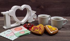Two white cups of coffee, cookies in the shape of a heart, red candle and a Valentine card on a wooden table. On Valentine's Day stock photos