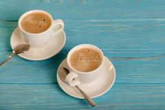 Two white cups of coffee on a wooden blue background. Selective focus Stock Photos