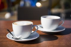 Two white cups of coffee on wooden table royalty free stock images