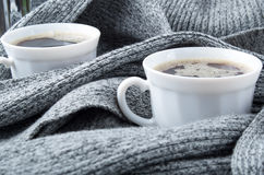 Two white cups of coffee wrapped in scarf Royalty Free Stock Photo