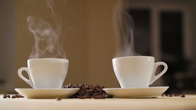 Two white cups of delicious coffee on the table with roasted beans in 4K.  stock footage