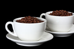 Two white cups, full of coffee beans. Isolated on black Stock Photos