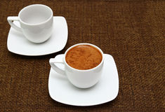 Two white cups with greek coffee on a sacking background Stock Image