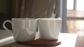 Two white cups with hot coffee and steam in the sun. Slow motion. 1920x1080. HD. Two white cups with hot coffee and steam in the sun. Slow motion stock footage