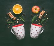 two white cups with ingredients for making New Year`s mulled wine, orange, cinnamon, anise and cloves, a black wooden backgroun stock photos