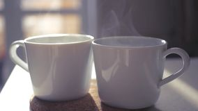Two white cups stand on a stoop in the rays of the sun, slow pairs are spinning in the light. slowmotion stock video