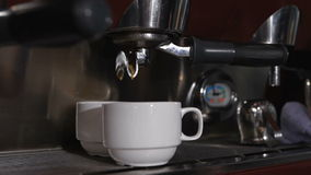 Two white cups standing on the grating of coffee machine and coffee pouring into them. Closeup stock footage