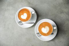 Two white cups of tasty cappucino with love art latte. stock photos