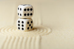 Two white dice with black dots on sand Royalty Free Stock Photos