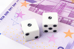 Two white dices with black dots are laying on 500 euro banknote Royalty Free Stock Image