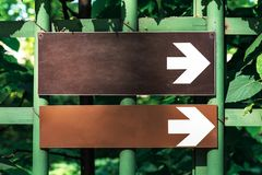 Two white directional arrow road sign point to the right in the park against the background of green trees.  stock images