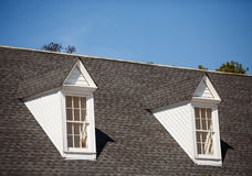 Two White Dormers on Grey Shingle Roof. Two white wood dormers on a grey shingle roof under blue sky Stock Photo