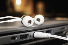 Two white earphones and mini jack plugged into laptop. Close up royalty free stock photos