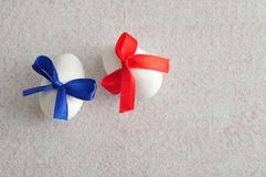 Two white easter eggs with different color bows Royalty Free Stock Image