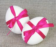 Two White Easter Eggs with Purple Ribbon. Two White Easter Eggs Tied with Purple Ribbon on Bagging Stock Image