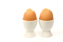 Two white egg cups with brown eggs Royalty Free Stock Photos