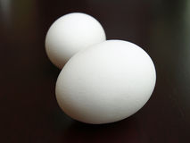 Two white eggs on a kitchen table Stock Photos