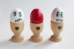 Two white eggs looking at a colored one Royalty Free Stock Photo
