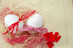 Two white eggs in a nest with red flowers Stock Image